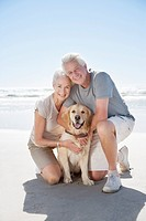 Senior couple with dog on beach