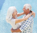 Senior Couple hugging poolside