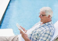 Senior man using digital tablet at poolside