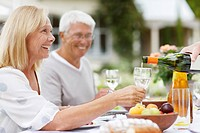 Senior adults enjoying wine at patio table