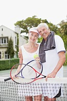 Senior couple hugging on tennis court
