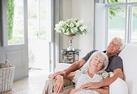 Senior couple sleeping on sofa in living room