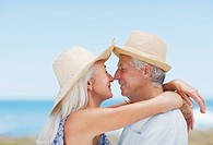 Senior couple in sun hats kissing on beach