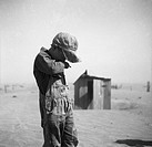 DUST BOWL, 1936.A farmer's young son covering his mouth during a dust storm in Cimarron County, Oklahoma. Photograph by Arthur Rothstein, April 1936.