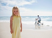 Girl standing on beach with father and brother playing in ocean