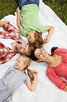 Happy family lying on blanket in grass, Munich, Bavaria, Germany