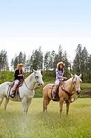 Two teen girls riding horses in Reardan, Washington, USA.