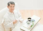 Senior Man Eating Meal at Bed