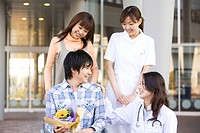 Patient with his doctor and nurse outside a hospital