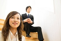 Businessman and businesswoman sitting on steps