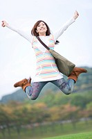 Young woman jumping with arms raised