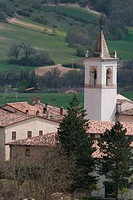 Detail aerial view of white church bell tower of Norcia, surrounding buildings and green fields beyond on sunny spring day