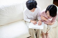 Young Couple Using Laptop on Sofa