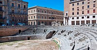 Roman amphitheatre with semicircular arena in foreground, shops, Renaissance, Baroque and modern facades beyond, in morning sunshine with blue sky, Le...
