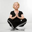 Caucasian senior woman sitting in yoga position on floor meditating.