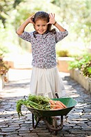 Cute girl standing near a wheelbarrow filled with carrots