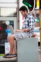 Man using a laptop near traffic light