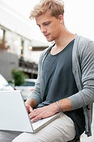 Young man using a laptop (thumbnail)