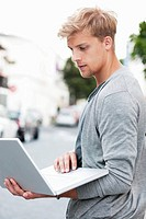 Young man using a laptop on a street