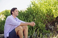 Mid adult man sitting on a rock in a garden