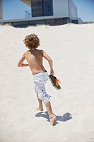 Rear view of a boy running on the beach