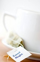 Close_up of a cup of herbal tea with a teabag on a saucer