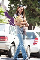 Beautiful young woman crossing a road with paper bags full of vegetables