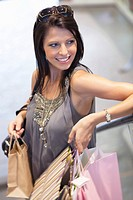Young woman holding shopping bags and smiling (thumbnail)