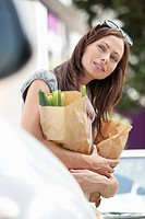 Beautiful young woman looking away and holding paper bags full of vegetables