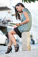 Young woman talking on a mobile phone and reading a book on a street