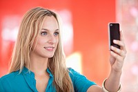 Young woman taking a picture of herself with a mobile phone