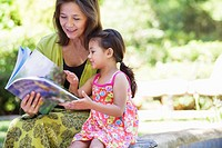 Woman with her granddaughter looking at a book