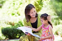 Woman with her granddaughter reading a book