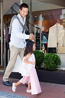 Cute little girl with her father walking out of a shopping mall with shopping bags