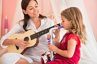 Woman playing guitar with her daughter playing saxophone (thumbnail)