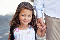 Portrait of a little girl holding her father's hand