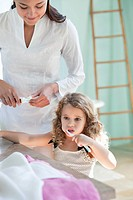 Cute little girl brushing teeth while mother looking at her