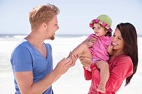 Couple enjoying on the beach with their daughter