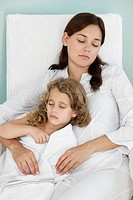 Young woman sleeping with little girl wrapped in towel