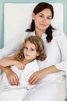 Portrait of a young woman lying with her daughter wrapped in white towel