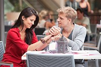 Young man holding hands of his girlfriend in a restaurant