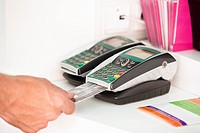 Sales clerk inserting a credit card in a credit card reader (thumbnail)