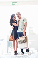 Smiling young couple standing with shopping bags