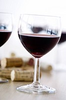 Close_up of glasses of red wine and corks