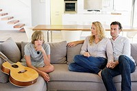 Couple looking at their son sitting near a guitar