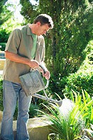 Mature man watering plants in a garden