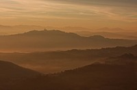 Sunrise over Tiber valley with orange and golden sky in the early morning mist of winter , and hilltop town of Todi in distance