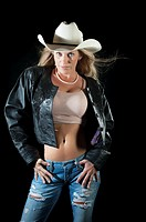 Attractive cowgirl in leather jacket and cowboy hat posing on black background