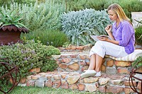 Beautiful young woman reading book in garden