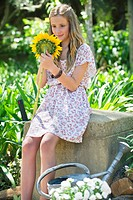 Cute little girl holding sunflower outdoors